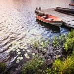 Rowboat at lake shore at sunrise — Stock Photo