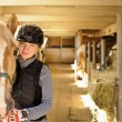 Rider with horse in stable — Stock Photo