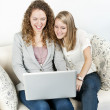 Two women using laptop computer — Stock Photo