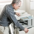 Man opening photocopier in office — Stock Photo