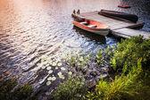 Rowboat at lake shore at sunrise — Stock Photo
