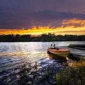 Boat docked on lake at sunset — Stock Photo