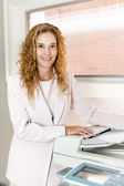 Businesswoman using photocopier in office — Stock Photo