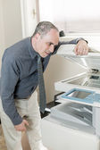 Man having problem with photocopier in office — Stock Photo