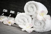 Rolled up towels and products at spa — Stock Photo