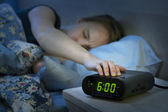 Woman waking up early with alarm clock — Stock Photo