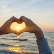 Hands in heart shape framing sun — Stock Photo #39362729