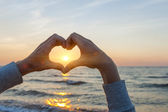 Hands in heart shape framing sun — Stock Photo