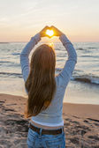 Girl holding hands in heart shape at beach — Stock Photo