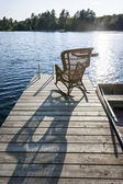 Rocking chair on small lake dock — Stock Photo