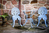 Patio furniture against stone wall — Stock Photo