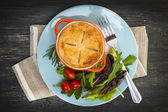 Homemade potpie meal with salad — Stock Photo