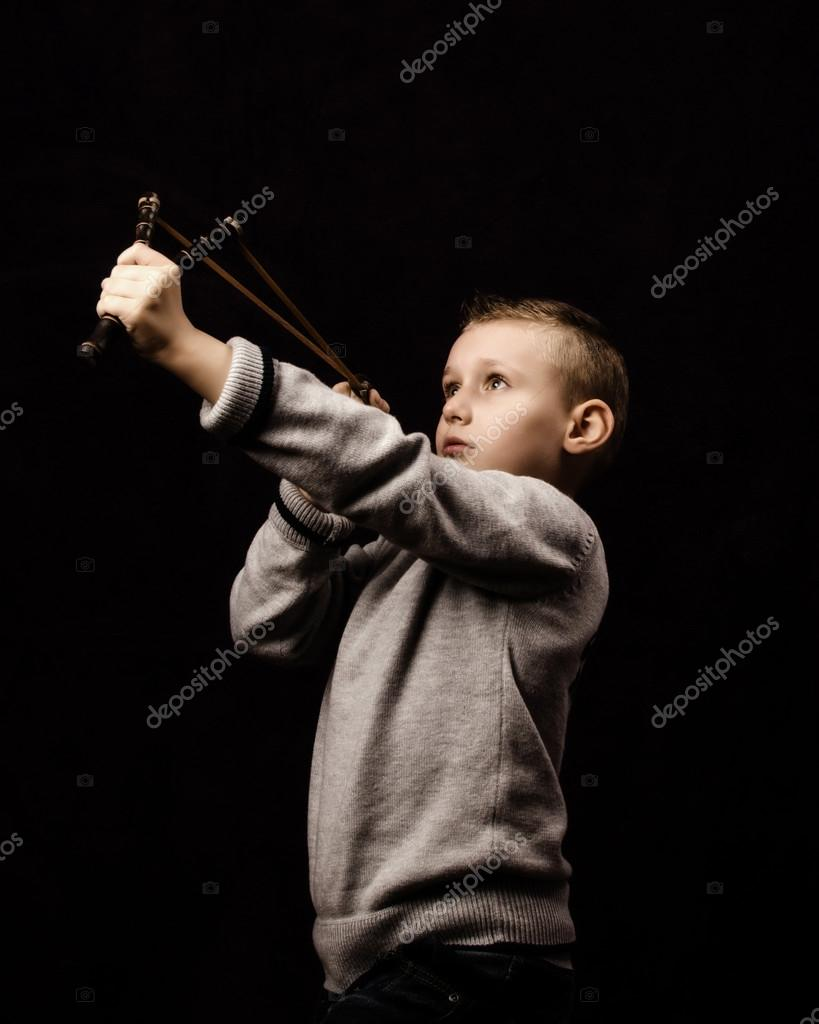 Little boy shooting with a slingshot — Stock Photo #14648701