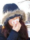 Young woman wearing furry hood, sneezes — Stock Photo