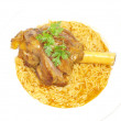 Lamb shank in juicy yellow rice - Stockfoto