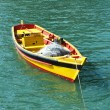 Small row boat floating on clear water — Stock Photo