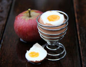 Egg and apple on wood — Stock Photo
