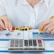 Hands holding pencil and pressing calculator buttons over documents — Stock Photo