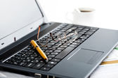 Laptop keyboard and pen and glasses — Stock Photo