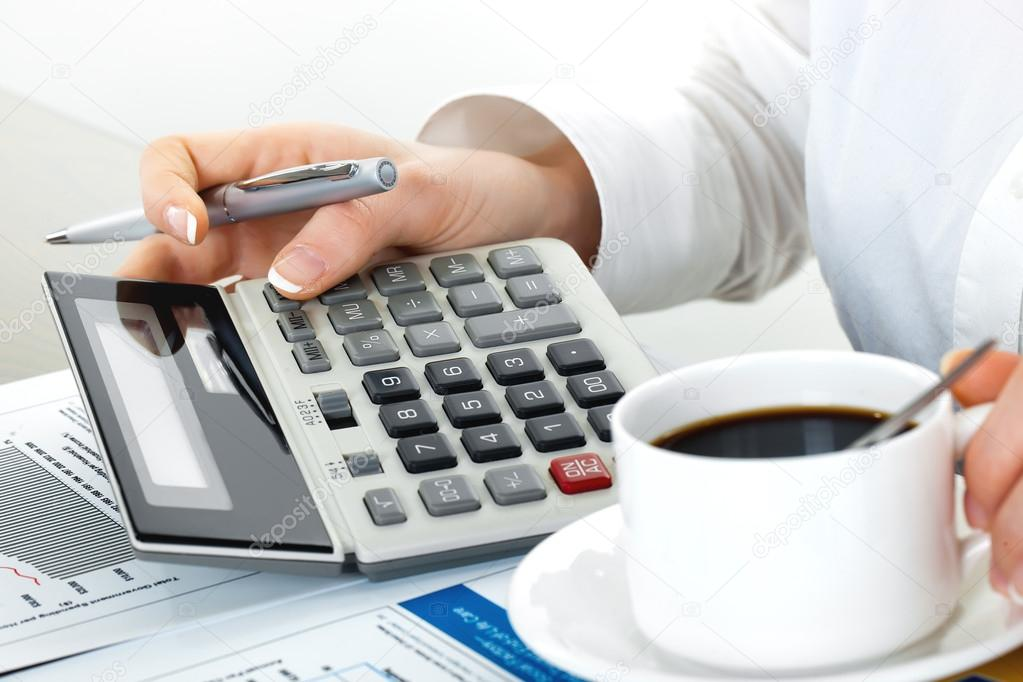 Hands holding pencil and pressing calculator buttons over documents  Stock Photo #14523755