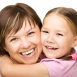 Stock Photo: Portrait of happy mother hugging her daughter