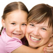 Stock Photo: Portrait of a happy mother hugging her daughter