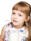 Cute little girl drinks milk using drinking straw — Stock Photo