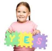 Cute little girl is holding Yes slogan — Stock Photo