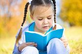 Mignonne petite fille lit un livre — Photo