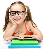 Cute cheerful little girl reading book — Stock Photo