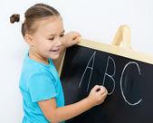 Kleines mädchen schreibt buchstaben auf einer tafel — Stockfoto
