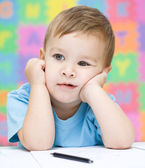 Little boy is writing using a pen — Stock Photo
