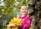 Linda niña está jugando con las hojas en el parque — Foto de Stock