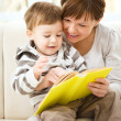 Stock Photo: Mother is reading book for her son