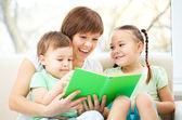 Annesi onu çocuklar için kitap okuyor — Stok fotoğraf