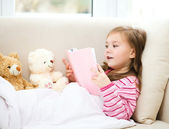 Little girl is reading a book for her teddy bears — Fotografia Stock