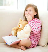 Little girl is reading a book for her teddy bears — Stock Photo