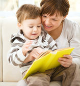Mother is reading book for her son — Stock Photo
