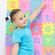 Little girl is pointing at letter N — Stock Photo