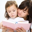 Mother is reading book with her daughter - Stok fotoğraf