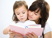 Mother is reading book with her daughter — Стоковое фото