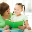 Mother is reading book for her daughter — Stock Photo