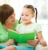 мать читает книгу для своей дочери — Стоковое фото