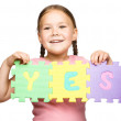 Cute little girl is holding Yes slogan — Stockfoto #16467241