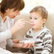 Stock Photo: Cute little boy is fed using spoon