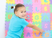 Little girl is pointing at letter G on alphabet — Stock Photo