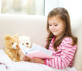 Little girl is reading a story for her teddy bears — Stock Photo
