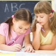 Little girl is writing using a pen — Stock Photo #17016835