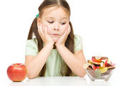 Little girl choosing between apples and sweets — Stock Photo