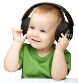 Cute little boy enjoying music using headphones — Stock Photo
